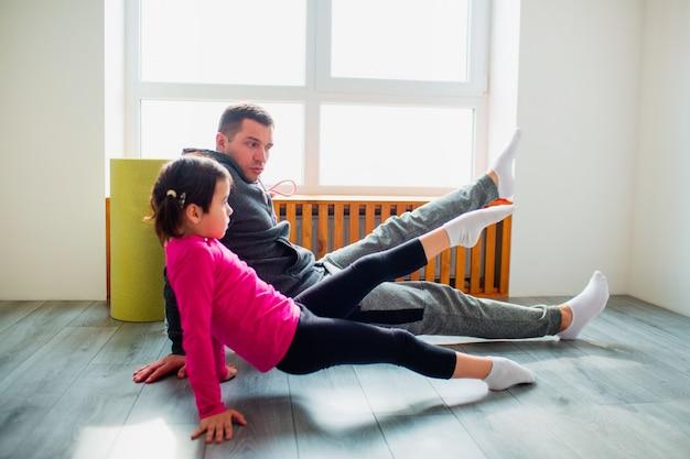 Il giovane padre e la sua piccola figlia sveglia stanno facendo la tavola di riverenza con il sollevamento della gamba sul pavimento a casa. allenamento fitness familiare. carino bambino e papà si sta allenando su una stuoia al coperto vicino alla finestra nella stanza.