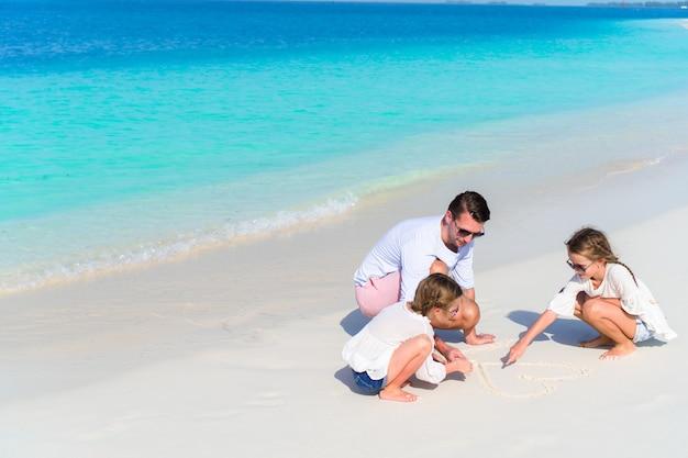 Il giovane padre e le sue adorabili figlie disegnano il cuore sulla sabbia bianca
