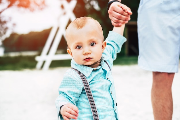 Il giovane padre felice con il piccolo figlio si diverte e imparando a camminare all'aperto nel parco