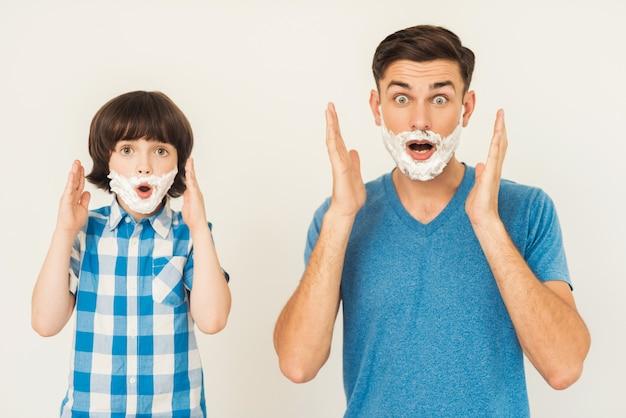 Il giovane padre insegna a little son a radersi a casa.