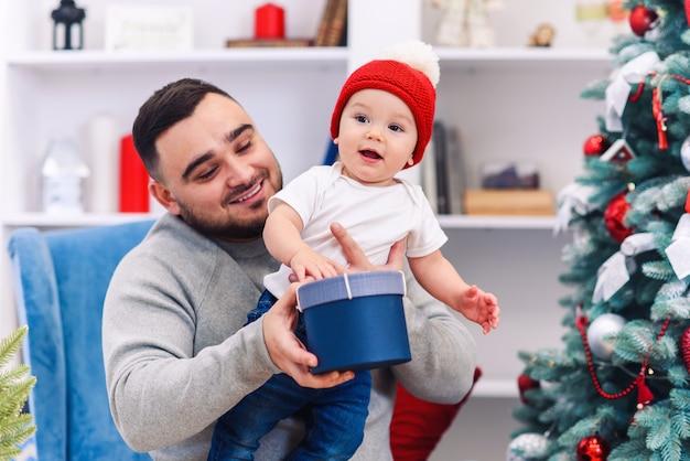 Il giovane padre si siede su una sedia comoda tenendo in braccio un bambino divertente e gli dà un regalo nella sala meravigliosamente decorata per festeggiare il natale.