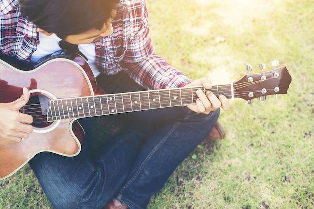 Il giovane pantaloni a vita bassa praticata chitarra nel parco, felice e godere p