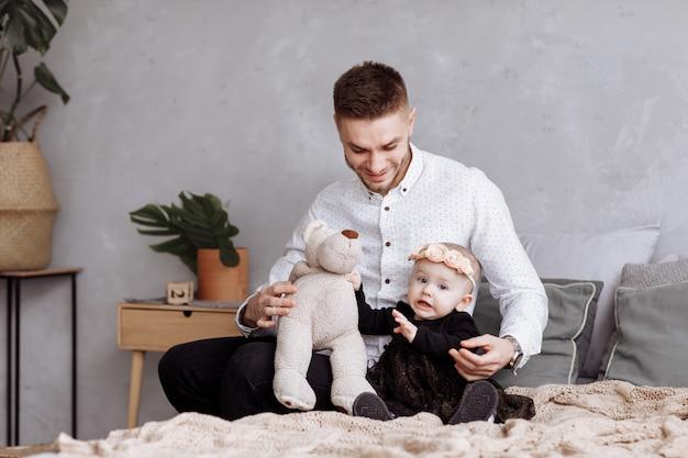 Il giovane papà bello e la sua neonata sveglia stanno sedendo e giocando con l'orsacchiotto sul letto a casa. papà, festa del bambino. la famiglia trascorre del tempo insieme