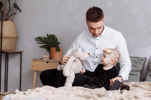 Il giovane papà bello e la sua neonata sveglia stanno sedendo e giocando con l'orsacchiotto sul letto a casa.