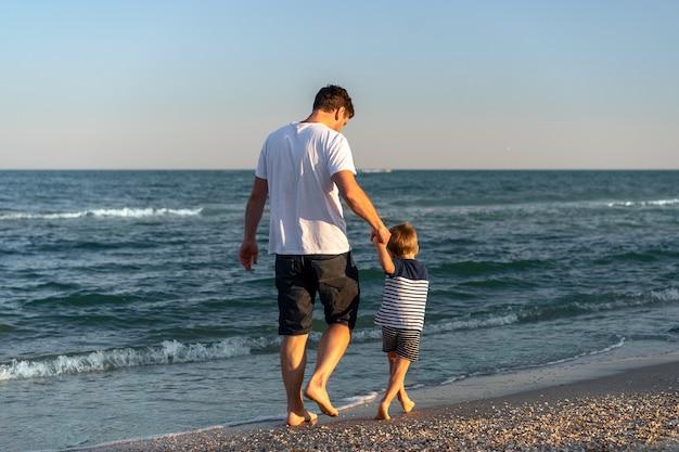 Il giovane papà caucasico con il piccolo figlio cammina al giorno di estate caldo della spiaggia del mare