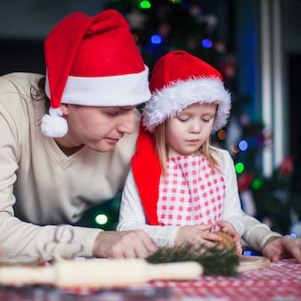 Il giovane papà con la piccola figlia in cappello di santa cuoce i biscotti del pan di zenzero di natale