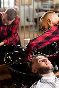 Il giovane parrucchiere che lava i capelli di un uomo
