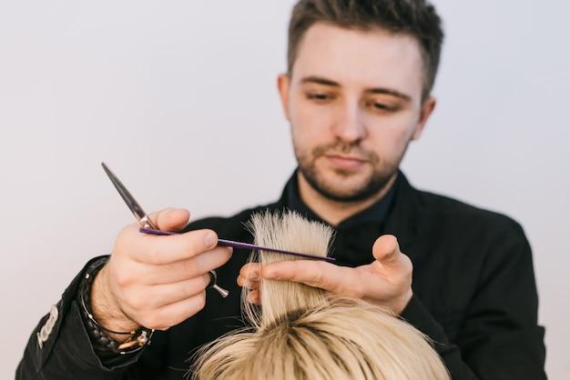 Il giovane parrucchiere tiene e taglia una ciocca di capelli bianchi della donna nello studio di bellezza.
