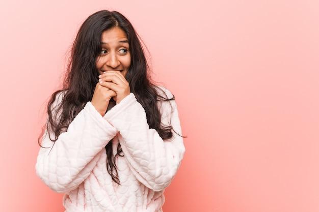 Il giovane pigiama da portare della donna indiana tiene le mani sotto il mento, sta guardando felicemente da parte.