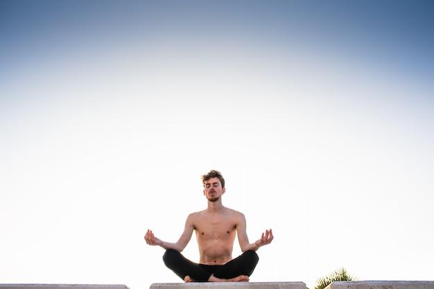 Il giovane professionista di yoga che la prepara pone, le gambe hanno attraversato la seduta su un parco del pavimento di legno nella città al crepuscolo, la posa del loto.