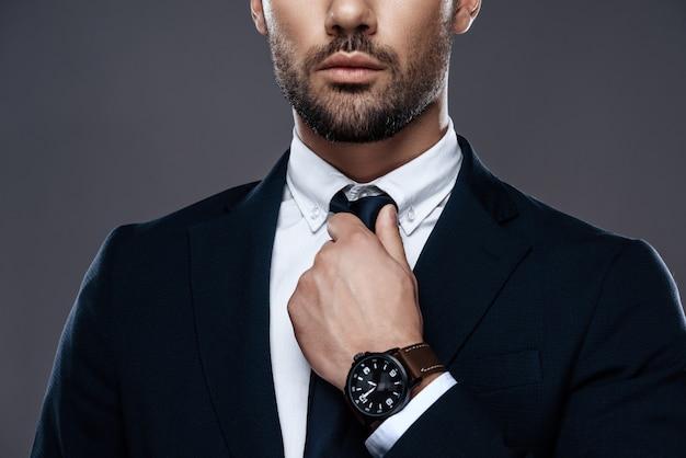 Il giovane raddrizza la cravatta, il viso con la barba lunga.