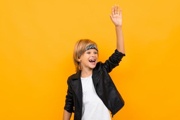 Il giovane ragazzo alla moda in giacca nera e maglietta bianca si rallegra