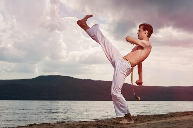 Il giovane ragazzo allena la capoeira