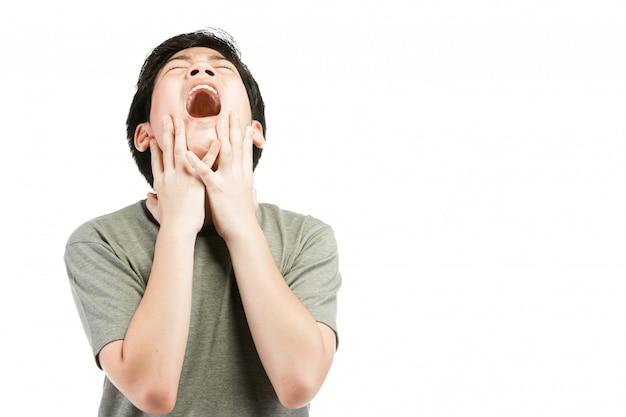 Il giovane ragazzo asiatico sopra priorità bassa bianca, è arrabbiato; avere un brutto carattere emotivo.