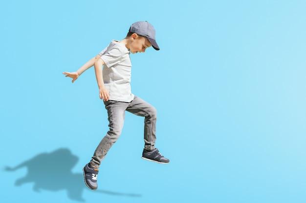 Il giovane ragazzo corre nel salto sulla strada su uno sfondo blu brillante