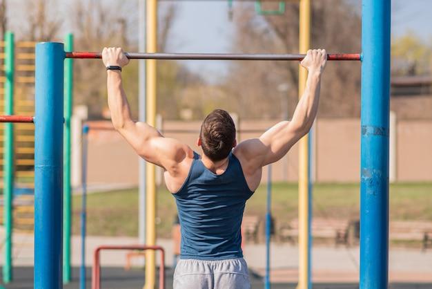 Il giovane ragazzo forte si tira su sulla barra orizzontale