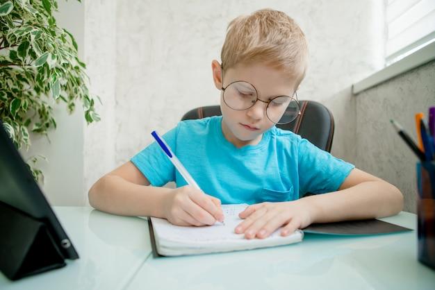 Il giovane ragazzo impara dalla compressa a casa. apprendimento a distanza in quarantena.