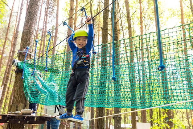 Il giovane ragazzo in casco cammina dalla corda