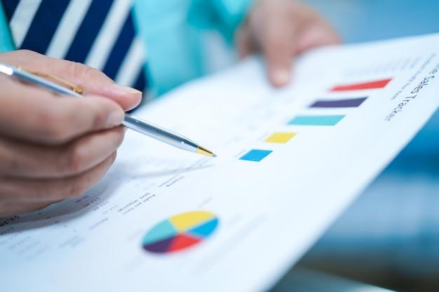 Il giovane responsabile astuto di affari che lavora con il nuovo progetto startup di successo analizza il piano del grafico.