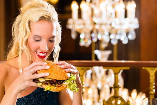 Il giovane ristorante di cucina raffinata mangia un hamburger, si comporta in modo improprio