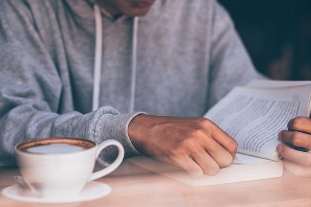 Il giovane sedeva sul divano e leggeva un libro sorseggiando un caffè caldo.