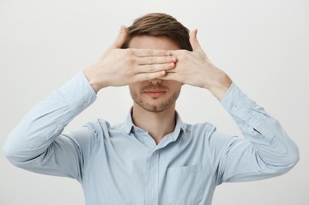 Il giovane serio copre gli occhi con le mani