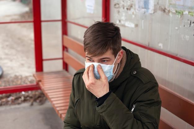 Il giovane si siede alla stazione degli autobus in primo piano monouso maschera medica.