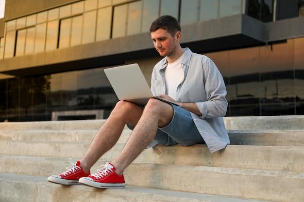 Il giovane si siede in gradini e lavora in laptop all'aperto.