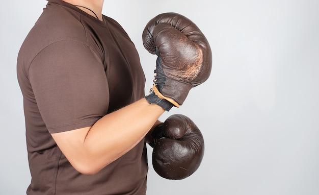 Il giovane si trova in un rack di boxe, indossando guantoni da boxe marrone vintage molto vecchi sulle sue mani