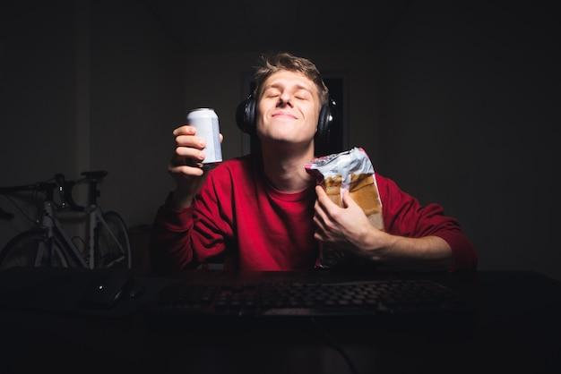 Il giovane soddisfatto con la cuffia avricolare sorride e tiene una bevanda con gli spuntini in sue mani