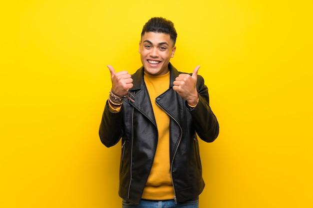 Il giovane sopra la parete gialla isolata con i pollici aumenta il gesto e sorridere