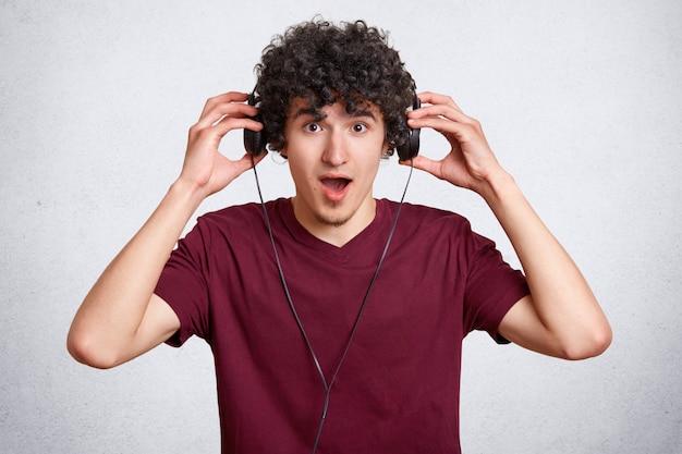 Il giovane sorpreso indossa le cuffie moderne