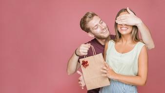 Il giovane sorridente che copre i suoi occhi delle amiche che tengono il sacchetto della spesa