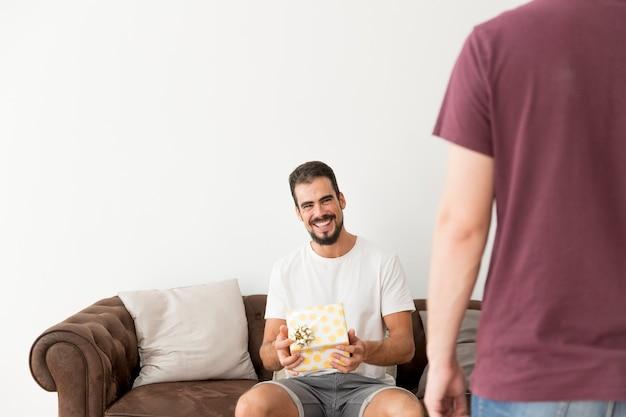 Il giovane sorridente che tiene il pois ha avvolto il contenitore di regalo con il suo amico