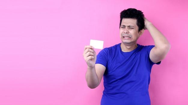 Il giovane spazio bello della carta di credito della tenuta dell'uomo dell'asia ha spaventato nella scossa con un fronte di sorpresa, impaurito ed eccitato con l'espressione di timore su fondo rosa in studio