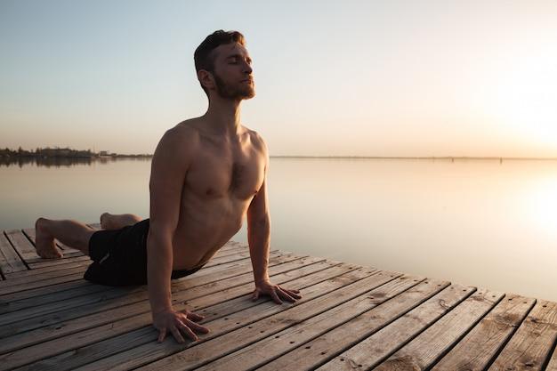 Il giovane sportivo bello fa gli esercizi di yoga alla spiaggia.