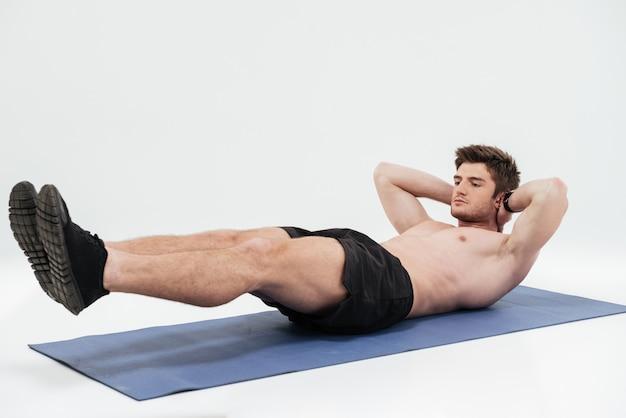 Il giovane sportivo che fa la plancia si esercita su una stuoia di forma fisica