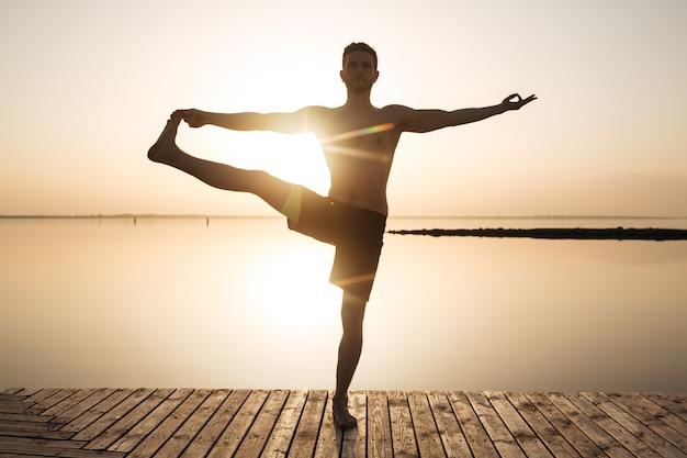 Il giovane sportivo concentrato fa gli esercizi di meditazione di yoga