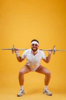 Il giovane sportivo felice fa gli esercizi di sport con il bilanciere