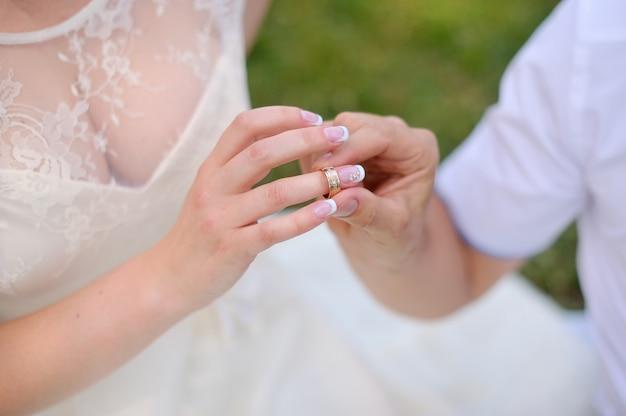 Il giovane sposo indossa la sposa dell'anello. isolato su sfondo bianco