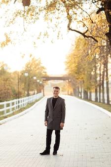 Il giovane sta camminando nel parco di autunno il giorno pieno di sole