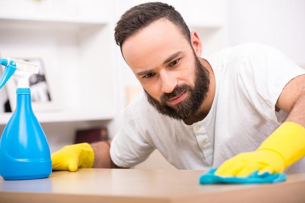 Il giovane sta facendo dei lavori di pulizia in casa.