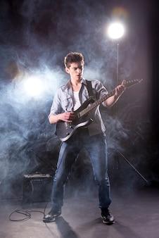 Il giovane sta suonando la chitarra contro nella stanza buia.