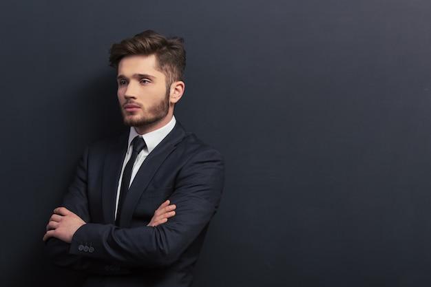 Il giovane studente bello in vestito classico sta distogliendo lo sguardo. sfondo di copyspace