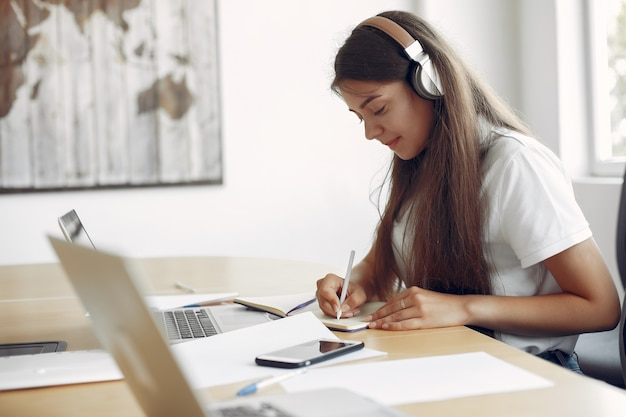 Il giovane studente che si siede alla tavola e usa il computer portatile