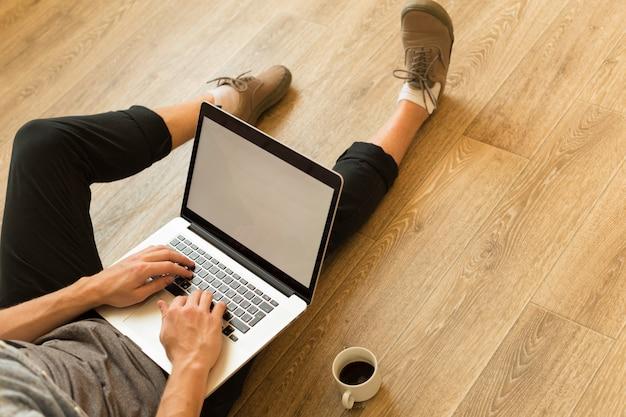 Il giovane studente lavora al suo computer portatile a casa