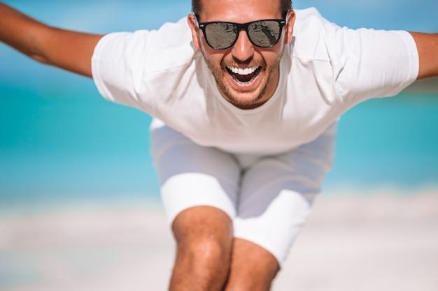 Il giovane sulla spiaggia si diverte e scherza