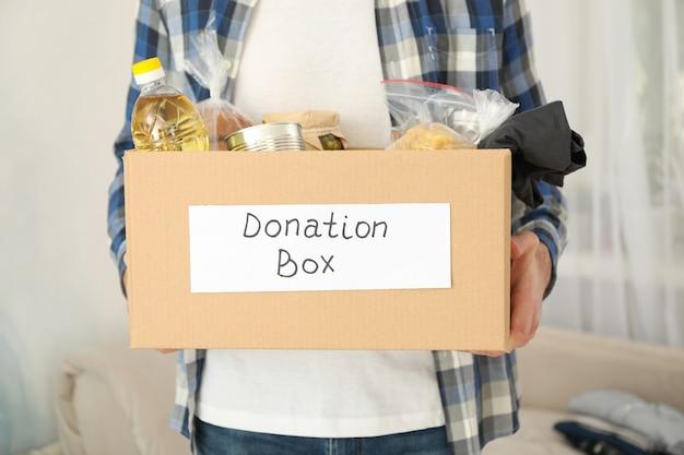 Il giovane tiene la scatola di donazione