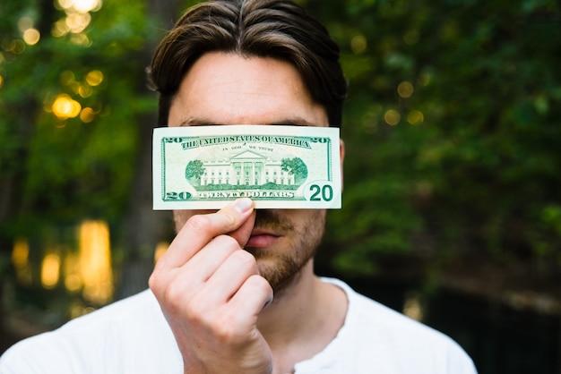 Il giovane tiene una banconota in dollari davanti al suo fronte, concetto di corruzione.
