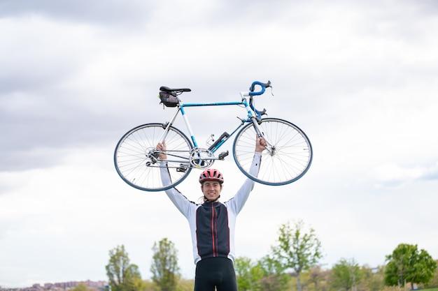 Il giovane tipo in casco e gli abiti sportivi che tengono la bicicletta sopraelevata con due armi contro il cielo nuvoloso in parco